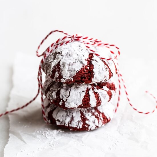 stack of red velvet crinkle cookies with bakers twine