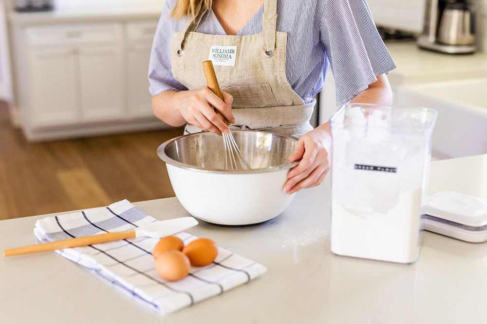 Tessa Arias in the kitchen with a mixing bowl baking