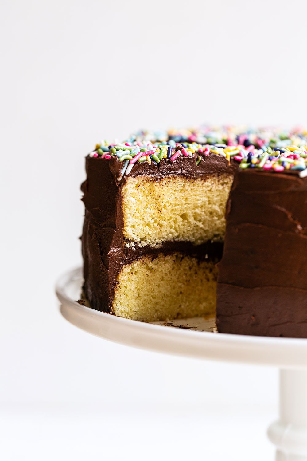 Yellow Layer Cake with Chocolate Frosting on a cake stand