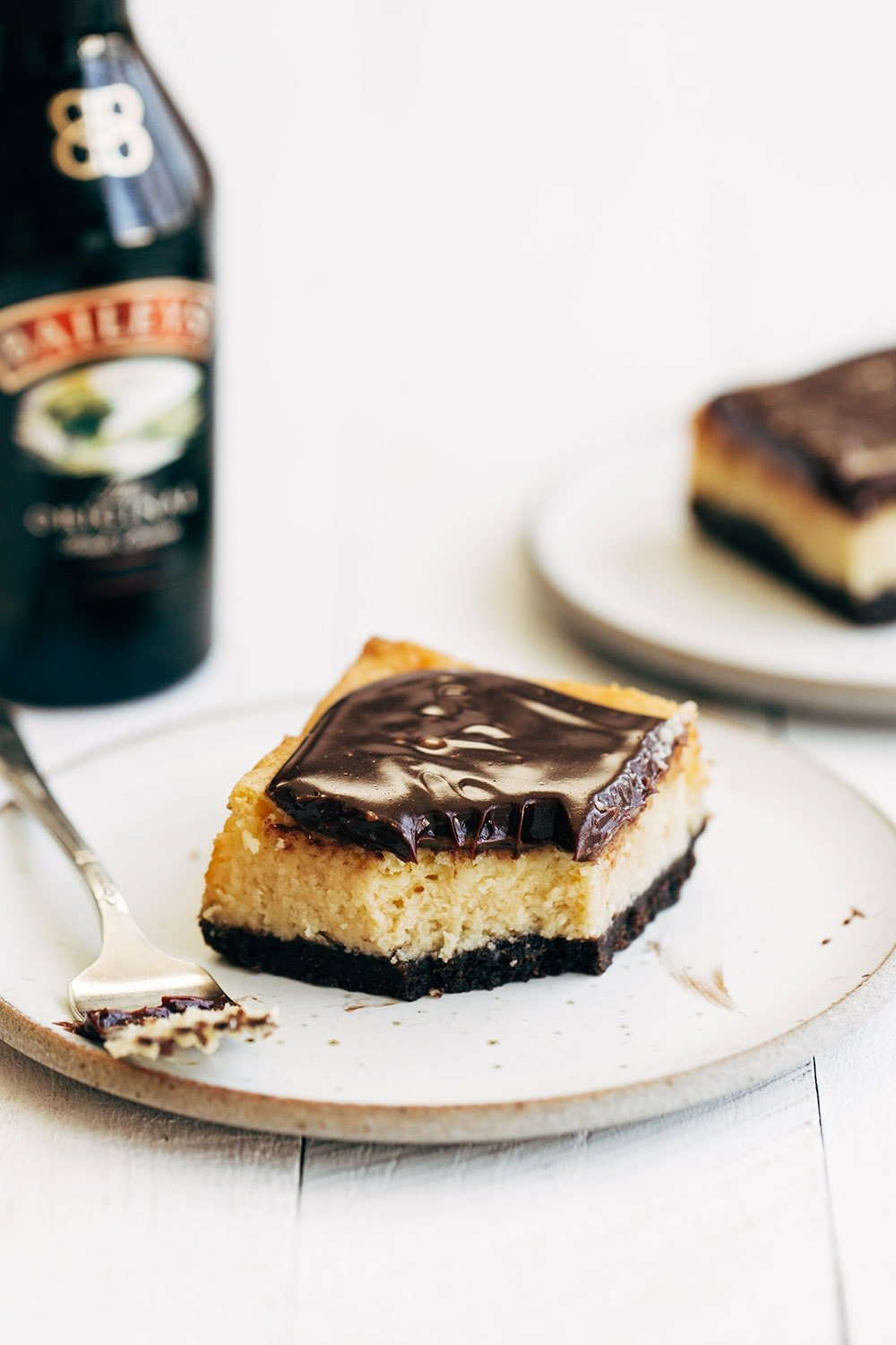 Bailey's cheesecake bar on a plate with a bottle of Bailey's Irish Cream