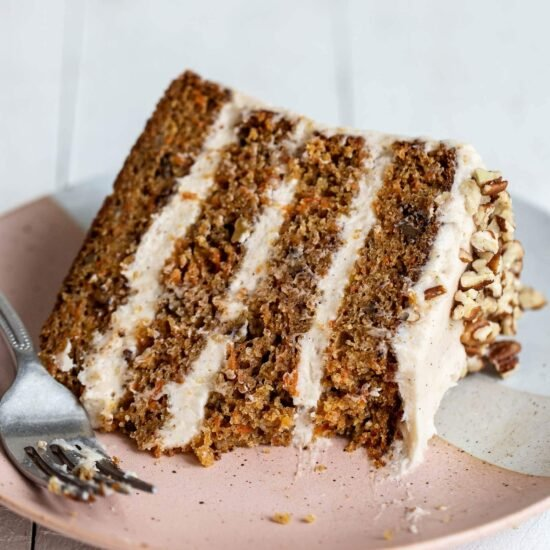 Slice of four layer brown butter carrot cake with cream cheese frosting on a plate with a forkful taken out