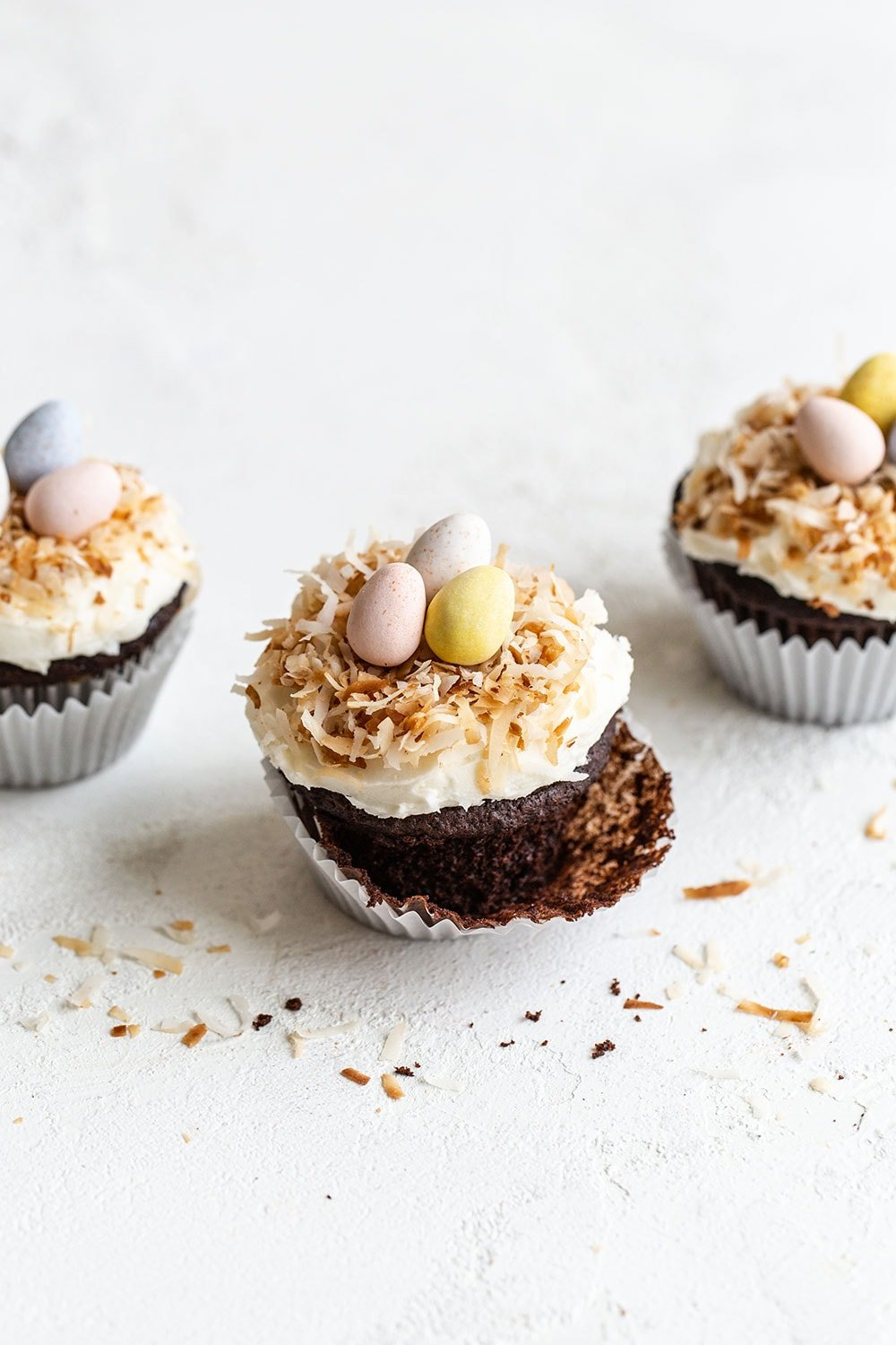 Three chocolate coconut cupcakes with toasted coconut
