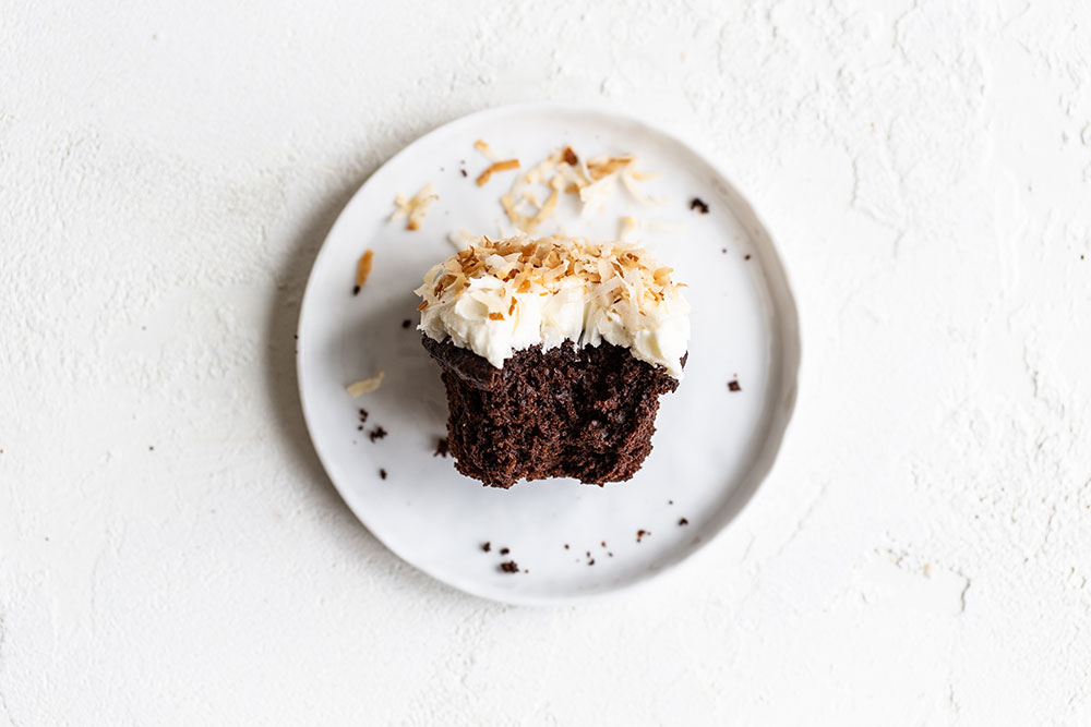 Chocolate coconut cupcake on a plate with a bite taken out