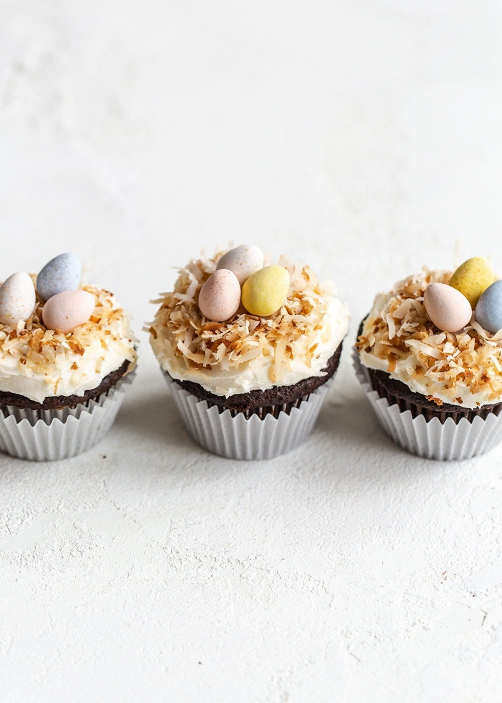 Row of three chocolate coconut cupcakes with Easter candies on top