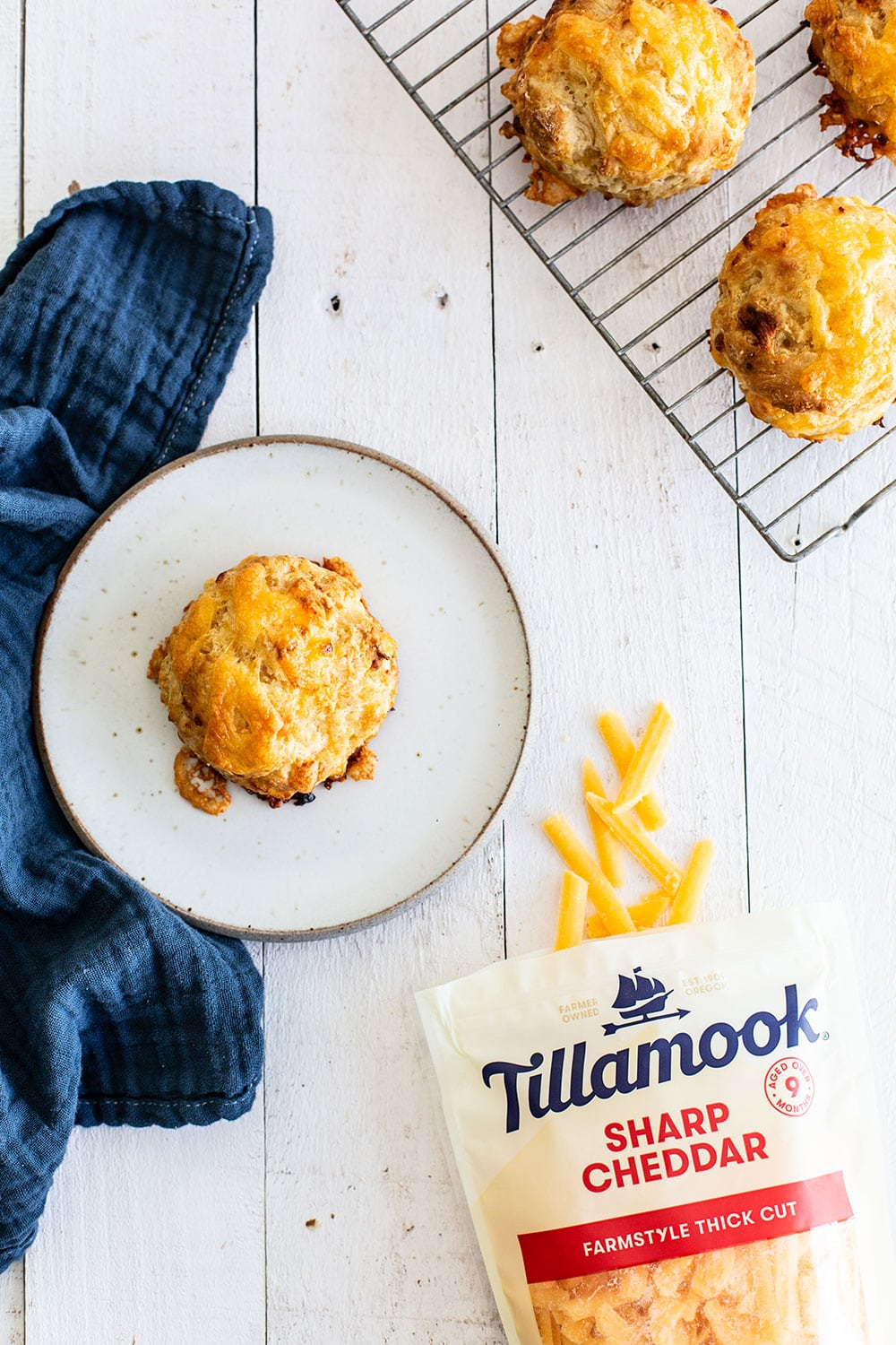 Cheddar biscuits cooling on a rack with one plated and a bag of Tillamook sharp cheddar shreds