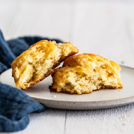 Cheesy cheddar biscuit cut in half on a plate