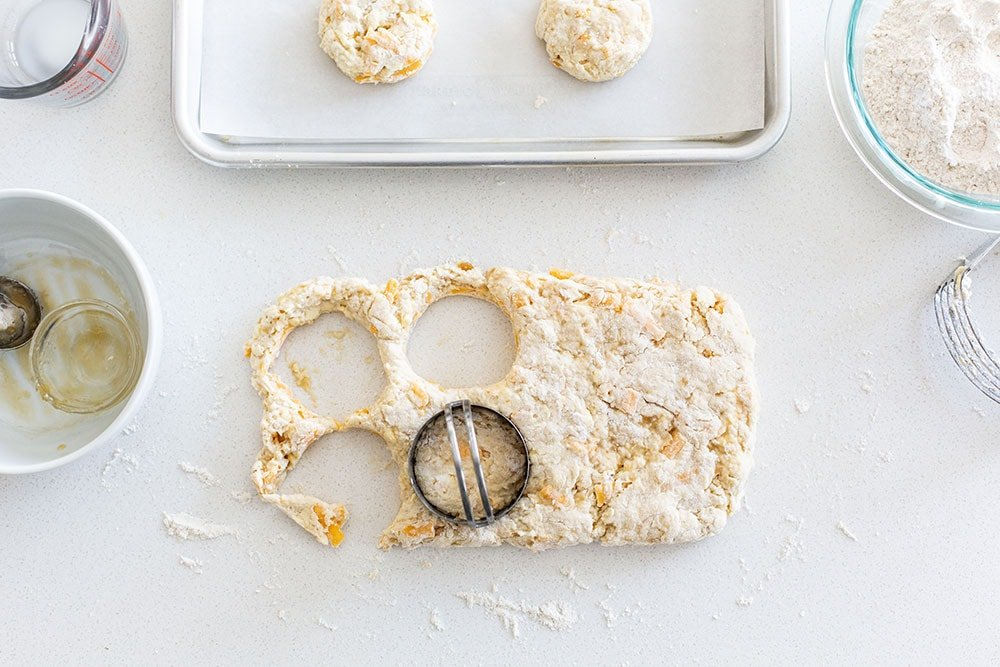 Homemade cheddar biscuit dough being cut into circles