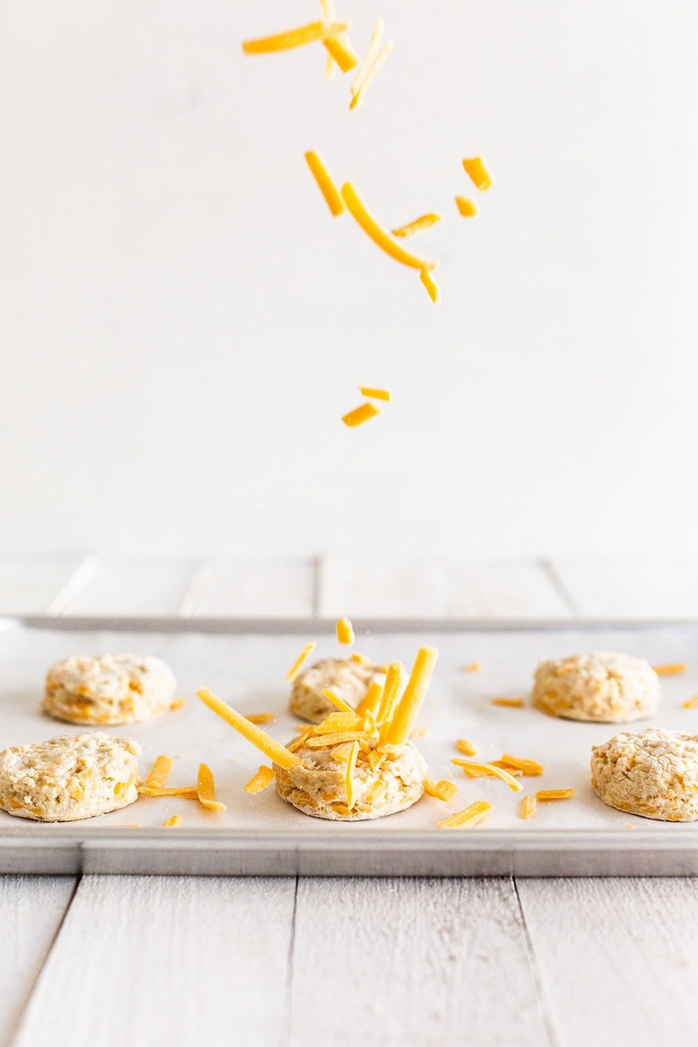 Sprinkling cheddar cheese on biscuit rounds before baking