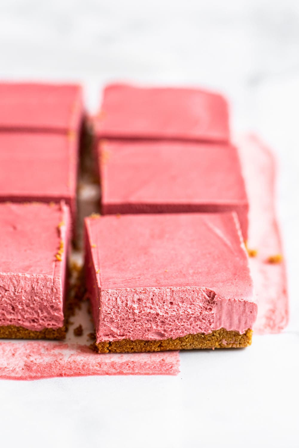 Row of no bake strawberry cheesecake sliced into perfect squares