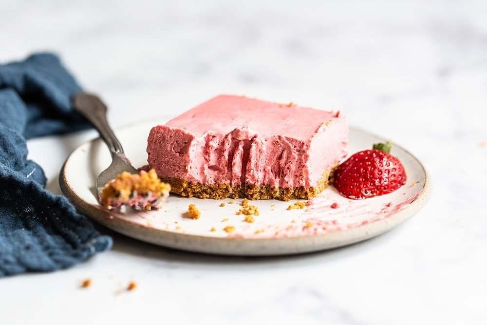 Homemade no bake strawberry cheesecake bar on a plate with a sliced strawberry on top