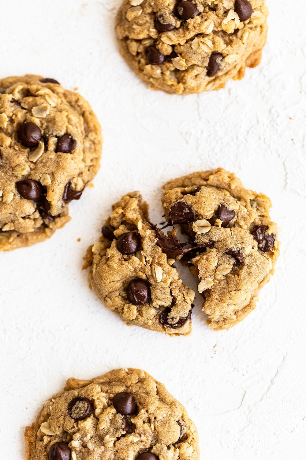 Peanut butter oatmeal chocolate chip cookies on the counter with one broken open with gooey chocolate chips