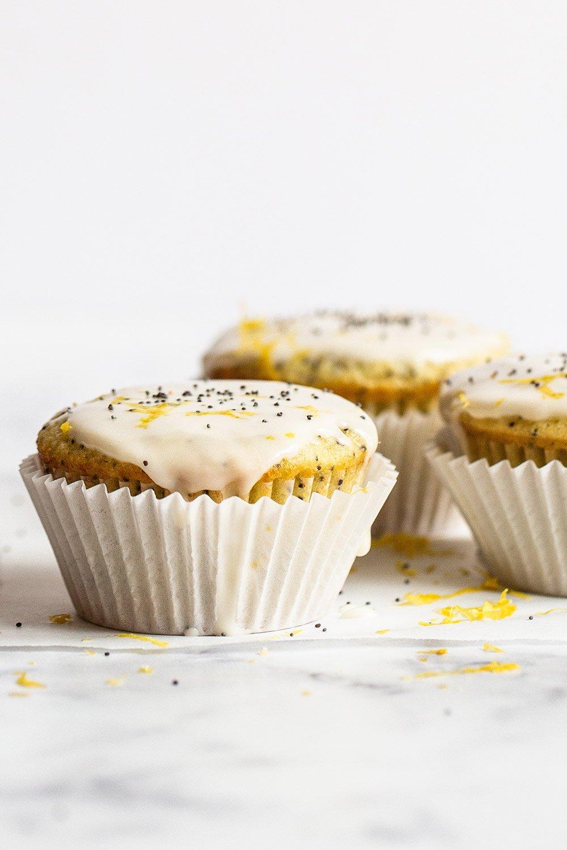 3 glazed lemon poppyseed muffins on a marble counter