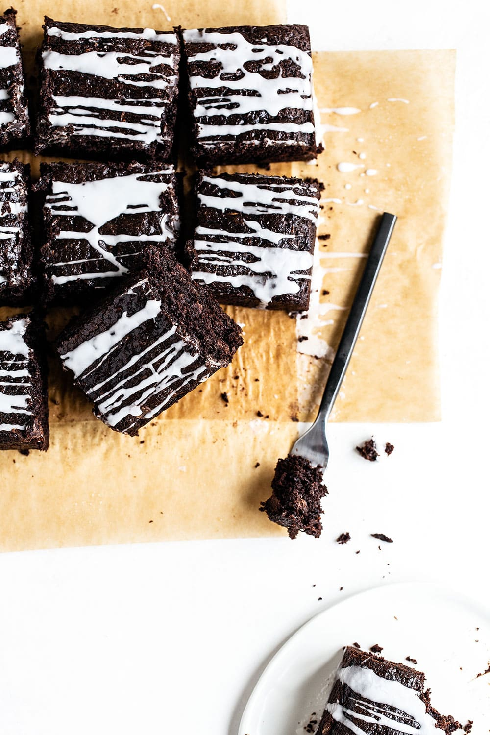Piece of chocolate zucchini snack cake on a plate with a fork