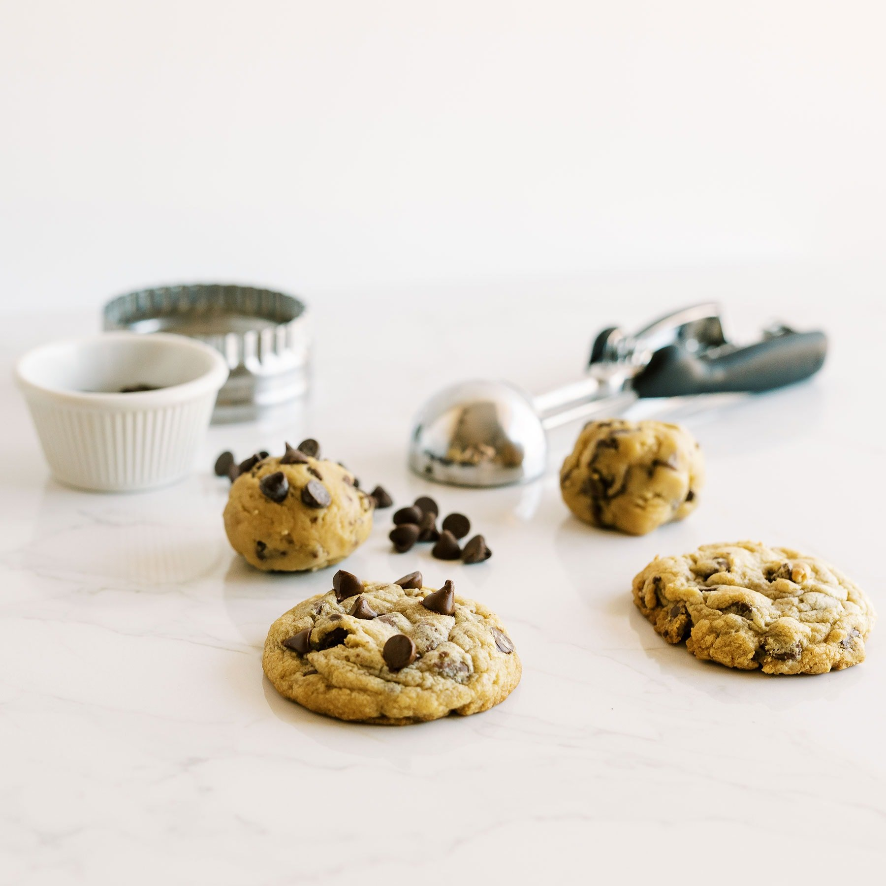 Cookie dough and baked cookies on a marble counter
