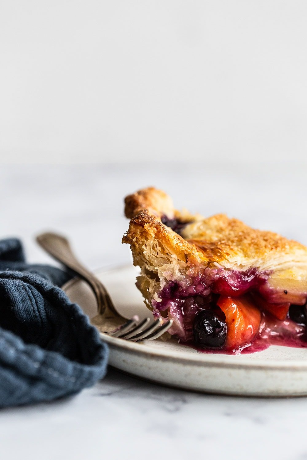 flaky piece of homemade blueberry peach pie