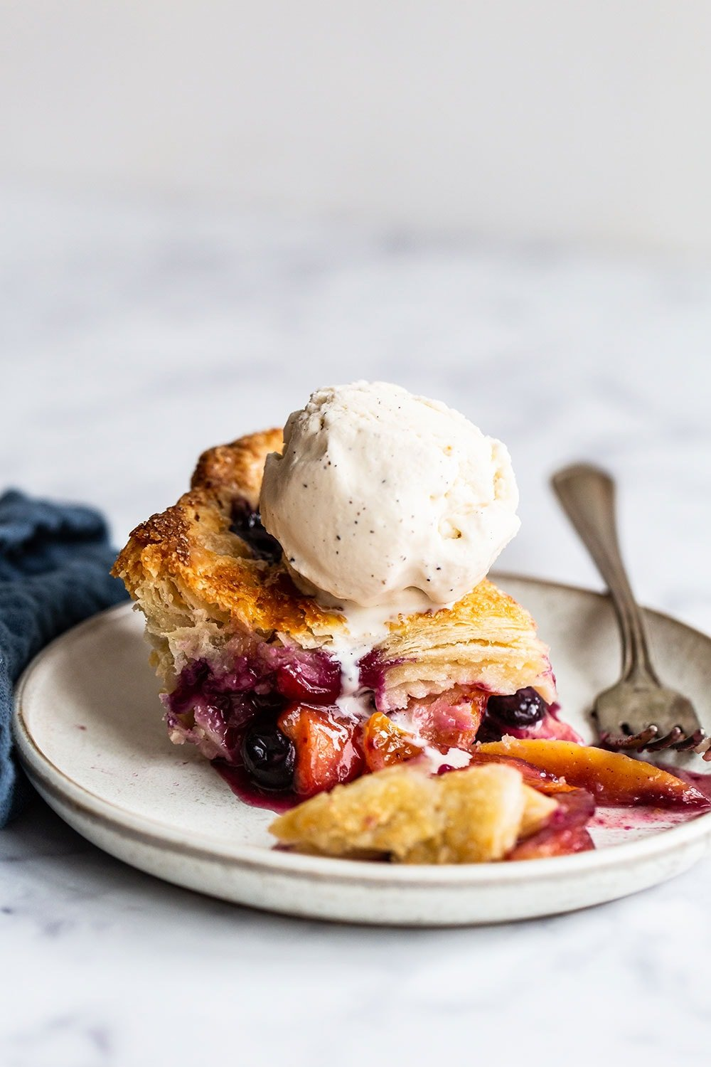 slice of blueberry peach pie with scoop of vanilla ice cream on top