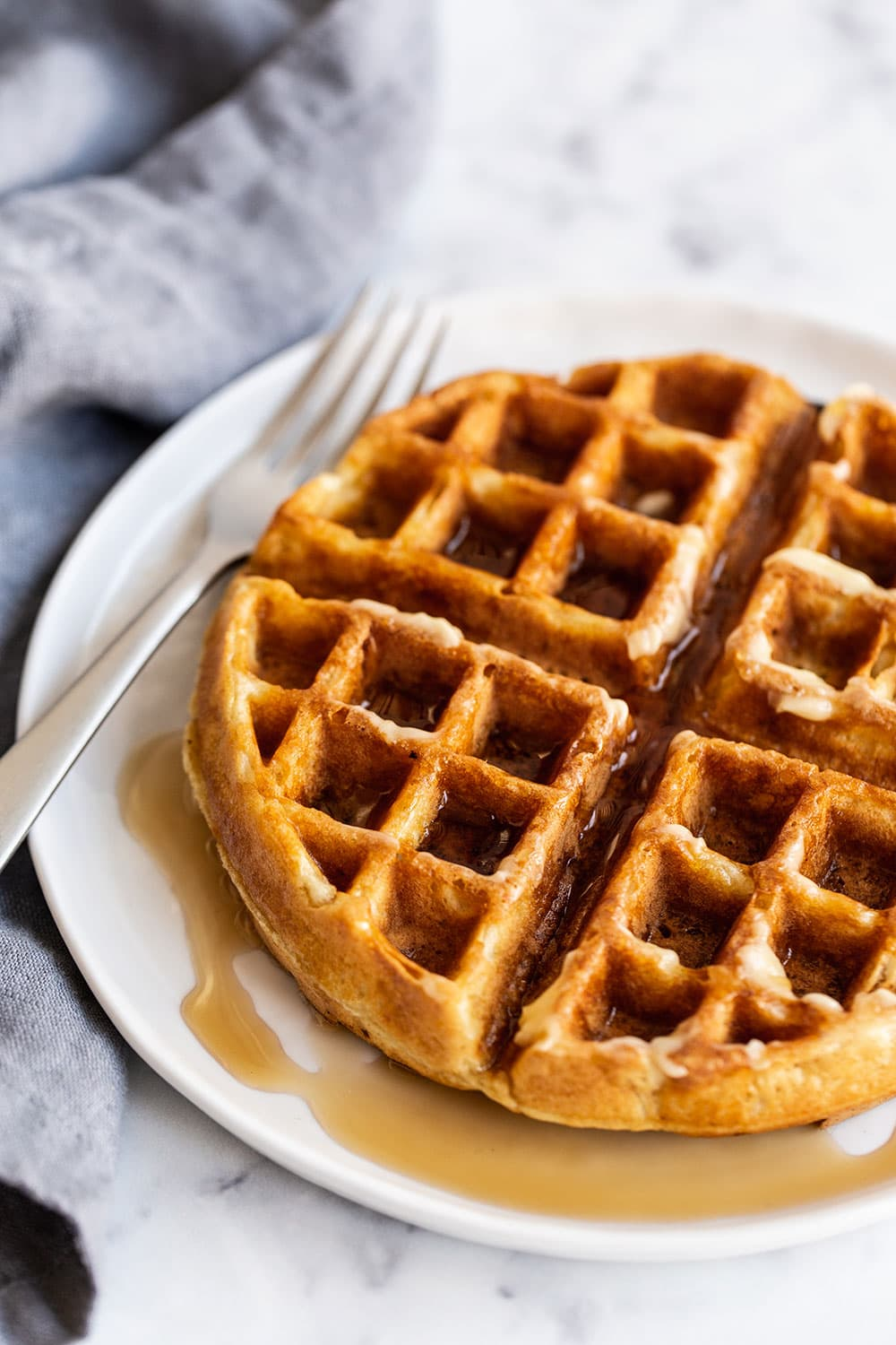 Homemade Belgian waffle on a plate with maple syrup