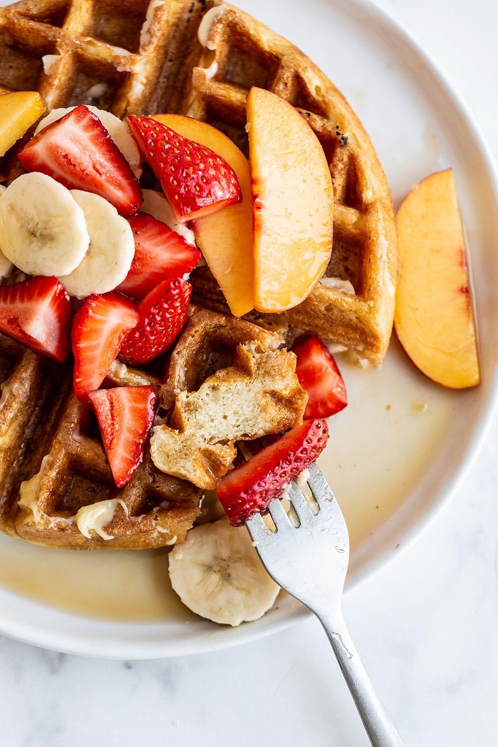 Waffle recipe on a plate with maple syrup and fresh fruit