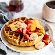 Homemade waffle on a plate with syrup and fresh fruit