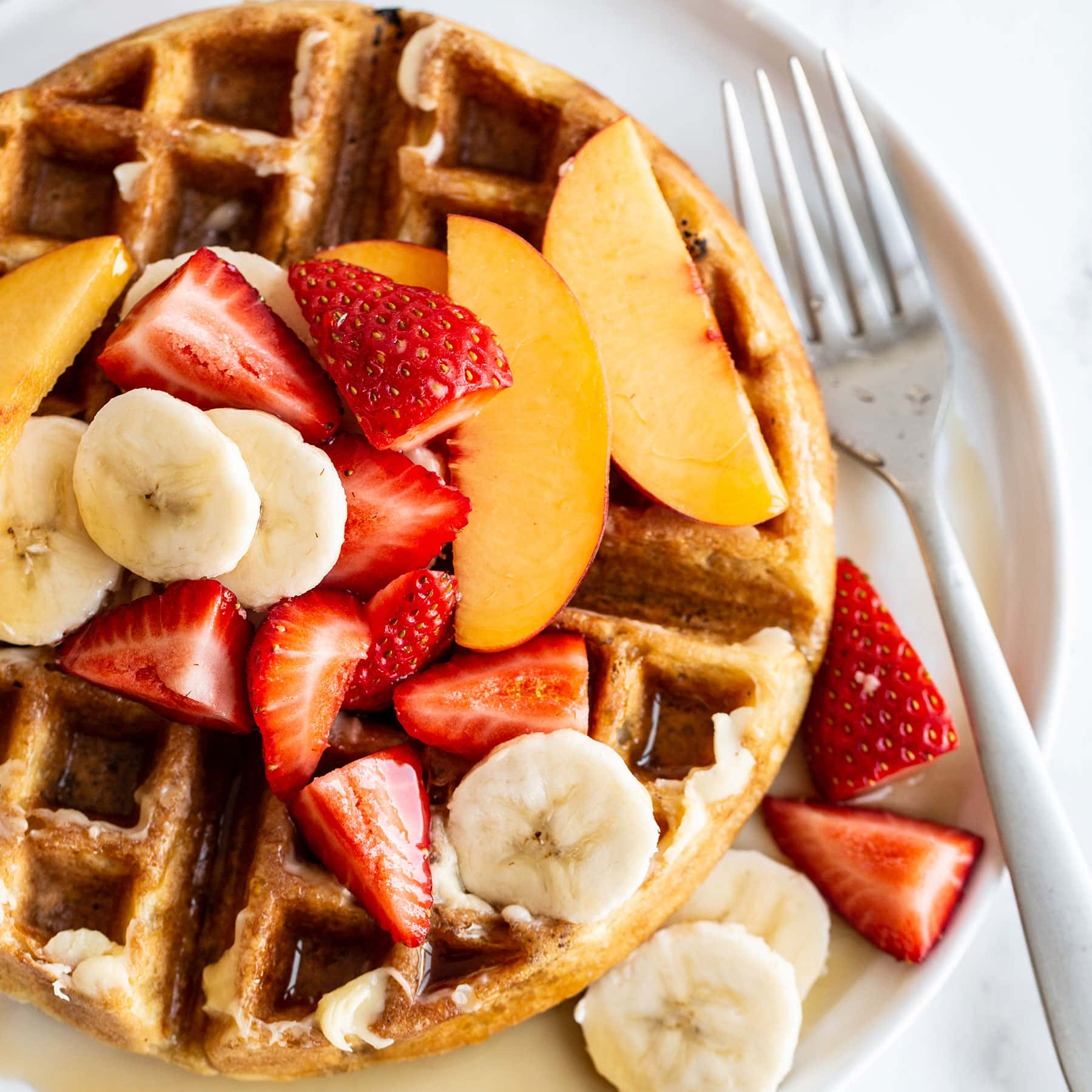 Homemade Belgian waffle on a plate with syrup and fresh fruit