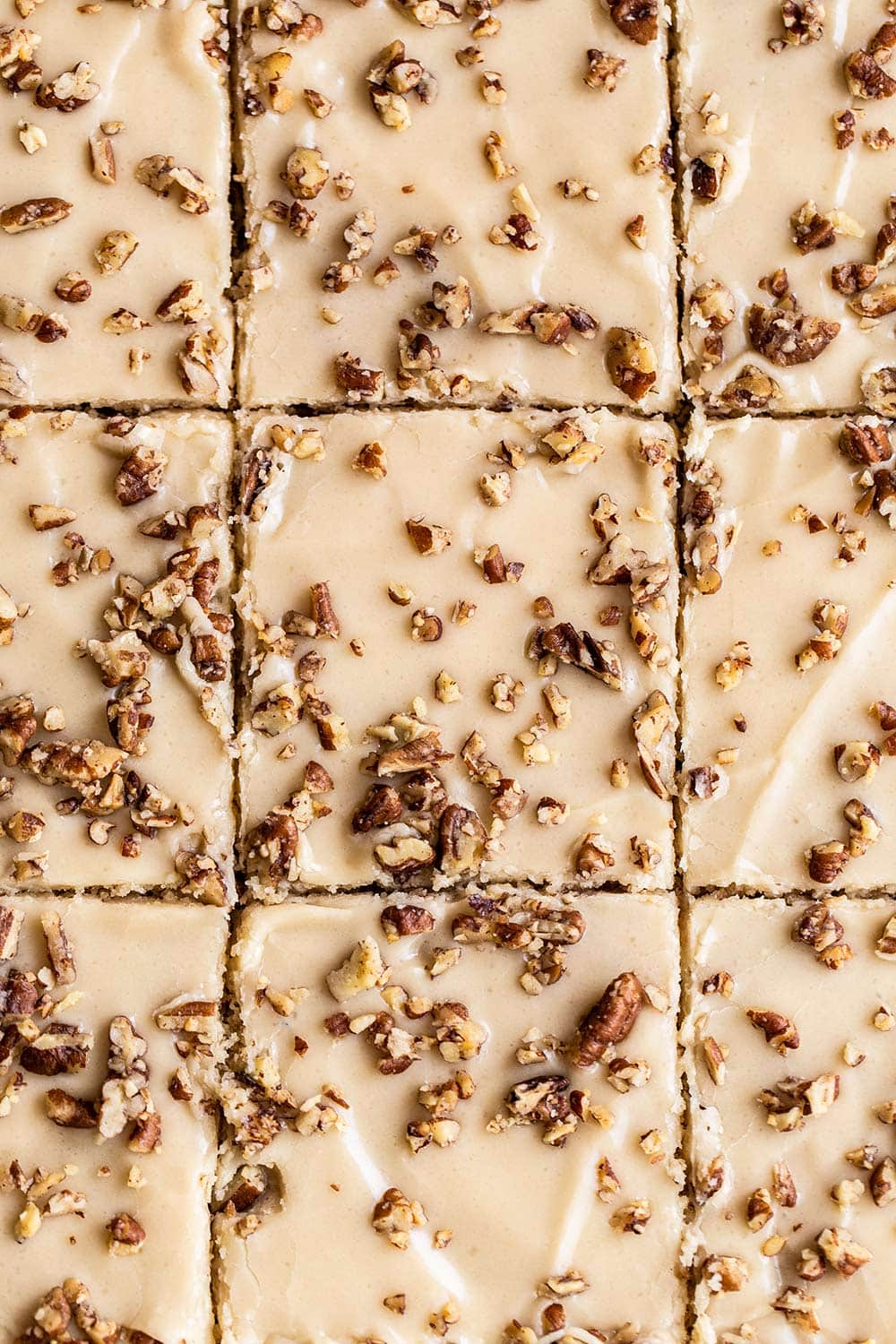 butter pecan sheet cake cut into squares with brown sugar frosting and chopped pecans on top