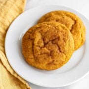 homemade pumpkin snickerdoodle cookies on a plate with a yellow towel