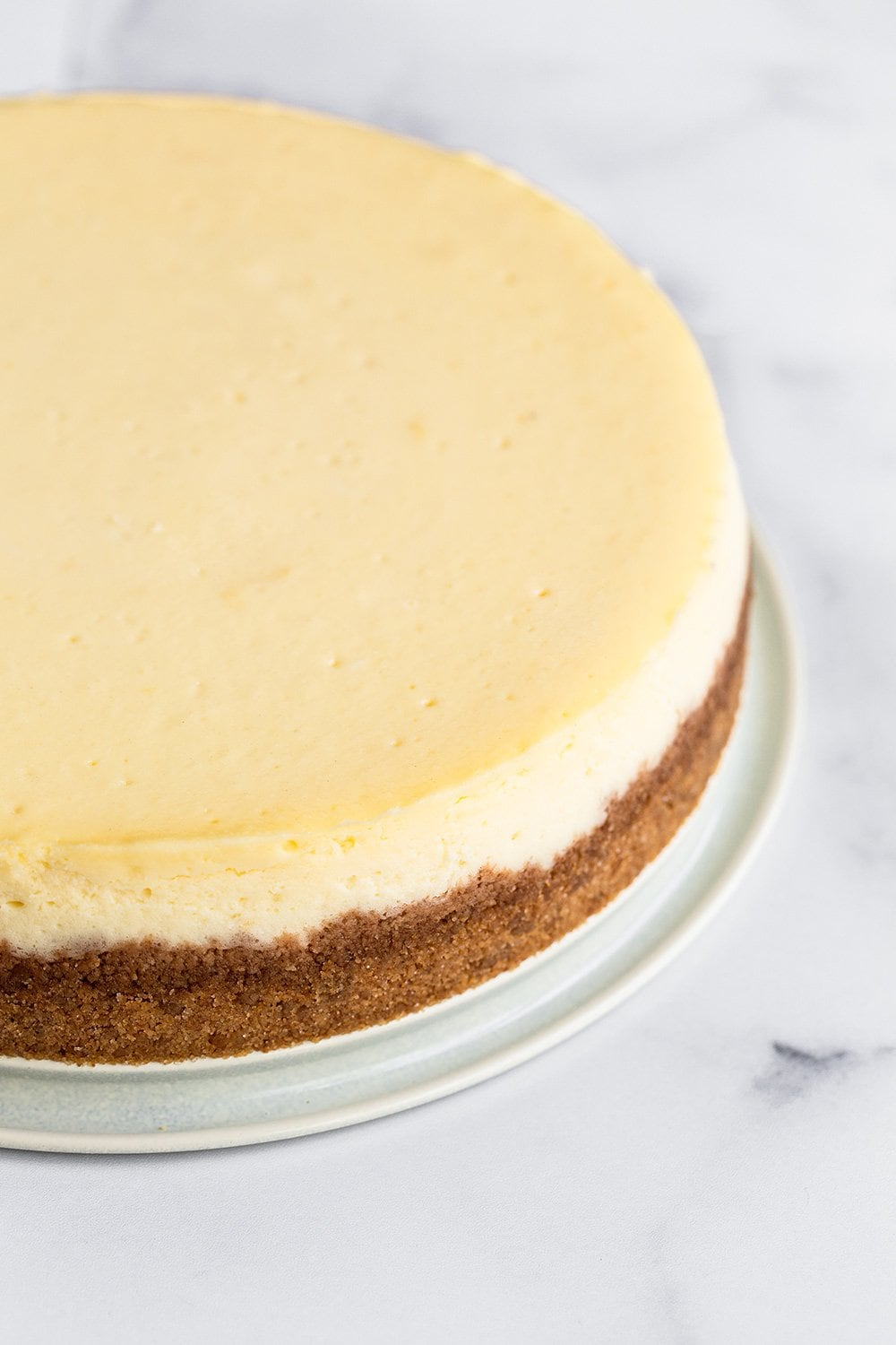 perfectly smooth and creamy cheesecake with no cracks and a graham cracker crust