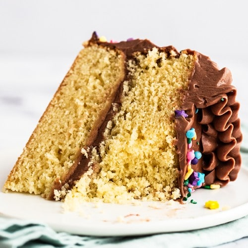 slice of homemade yellow fluffy cake and chocolate buttercream frosting