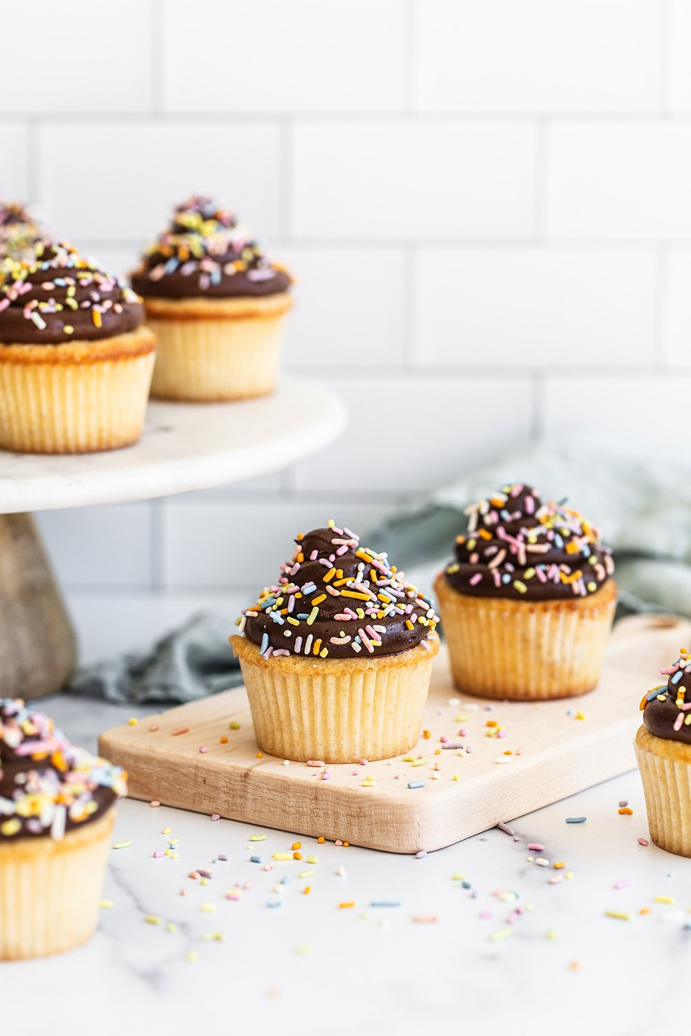 yellow birthday cupcakes with chocolate frosting and sprinkles on a wood board and platter behind