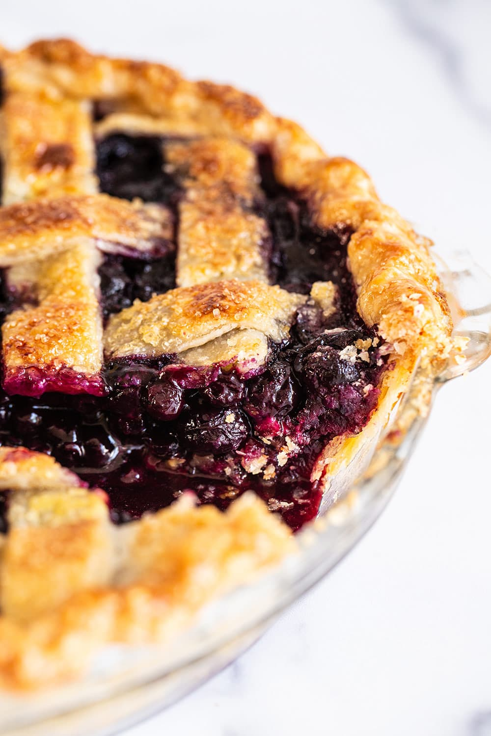 gooey blueberry pie filling with a flaky pie crust inside of a pie dish