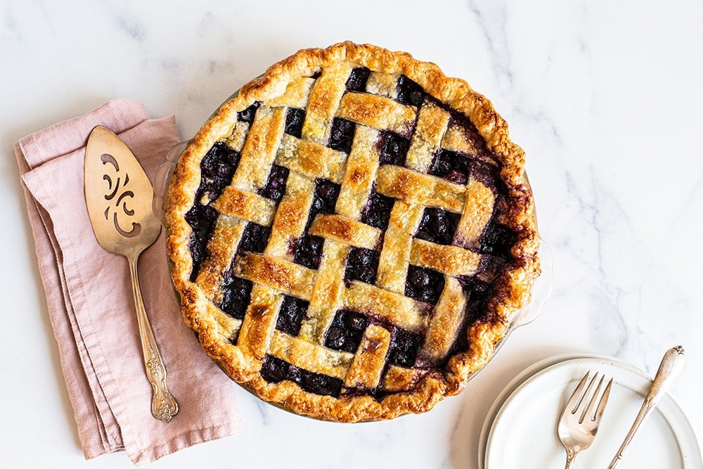 overhead shot of the best ever homemade blueberry pie recipe with a golden brown flaky crust