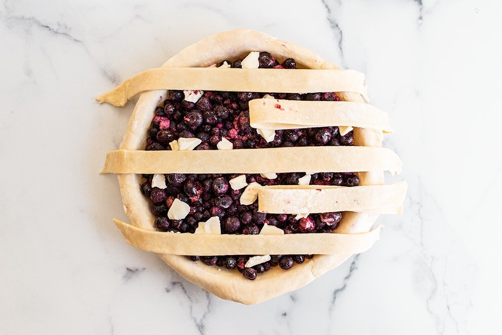 fold back the pie dough strips to the side to prepare a lattice pie crust