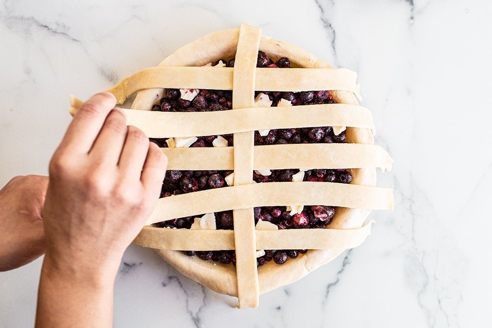 begin to layer your pie dough strips for a lattice pie crust
