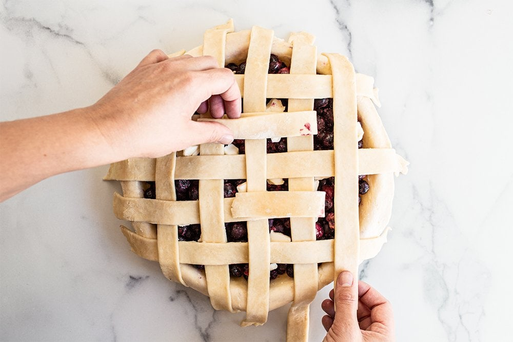finish adding all the strips to the pie dough for a lattice pie crust