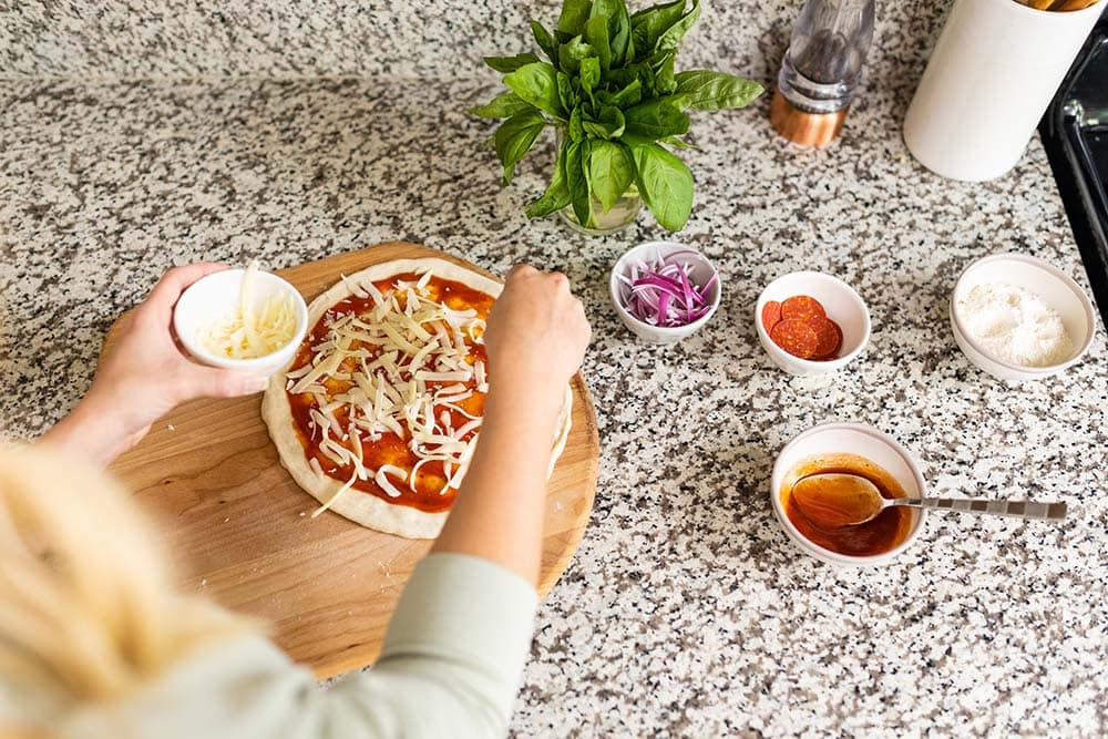 mozzarella cheese being sprinkled on top of a homemade pizza dough with bowls of pizza toppings on the side