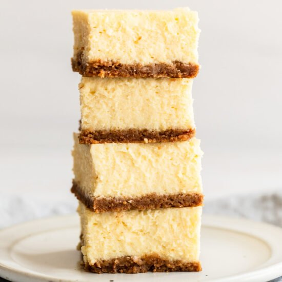 homemade creamy classic cheesecake bars stacked on top of each other