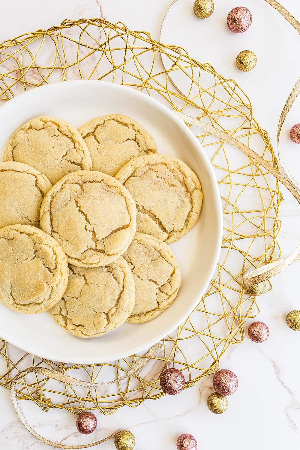 soft and chewy homemade sugar cookies on a plate with christmas ornaments surrounding