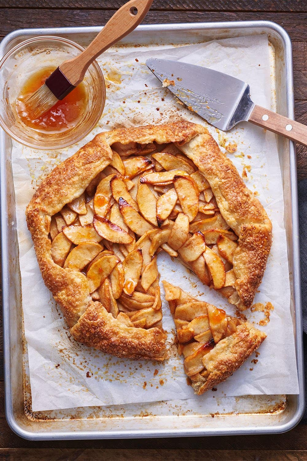 homemade rustic apple galette on a baking pan with parchment paper and apricot jam
