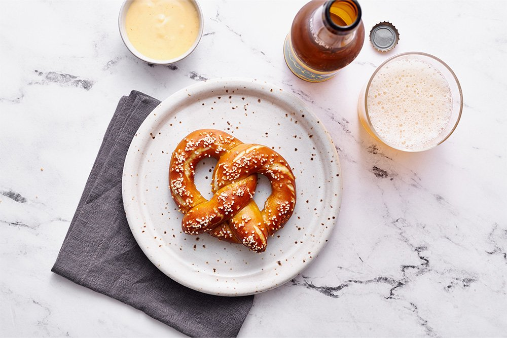homemade bavarian style pretzel on a plate with beer cheese and a glass of beer to the sides