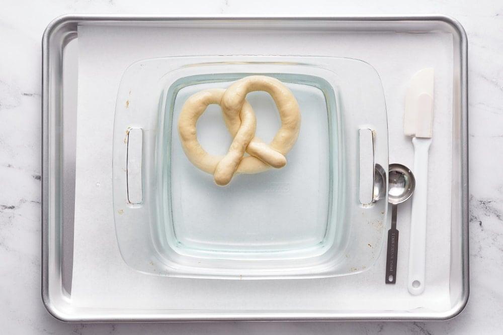 homemade pretzel in a glass dish for a lye bath