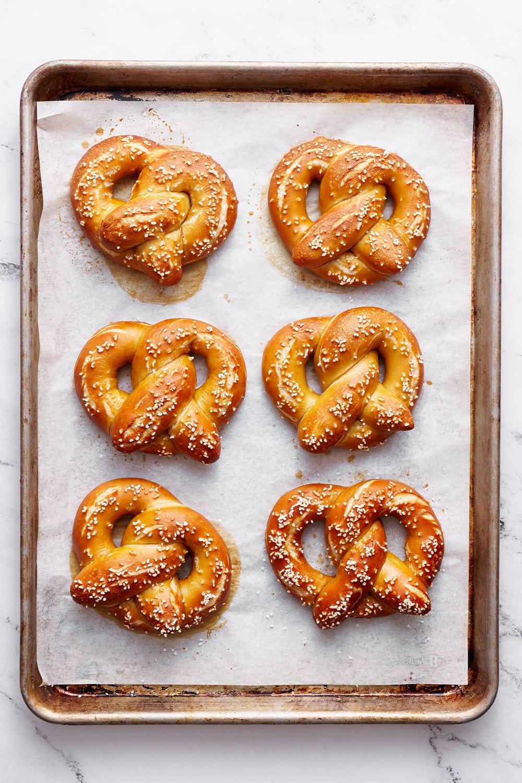 homemade pretzels on a baking sheet after being salted