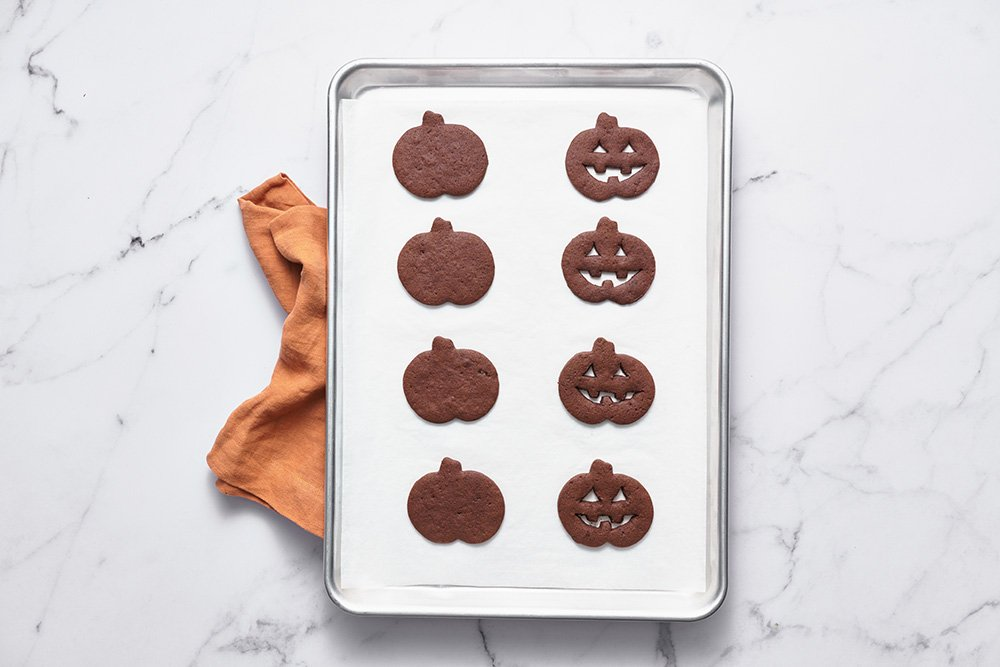 chocolate sugar cookies and jack o lantern cookies on a pan with parchment paper