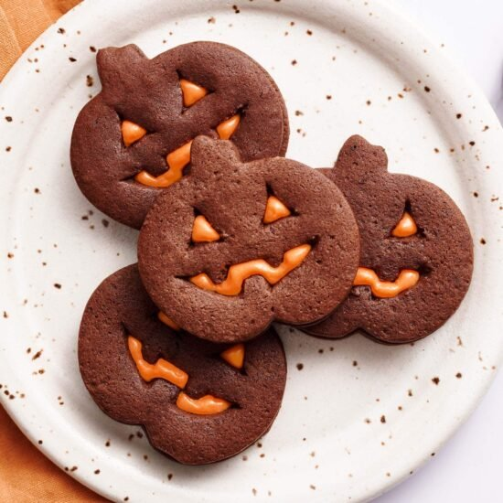 easy homemade jack o lantern cookies on a plate with an orange towel